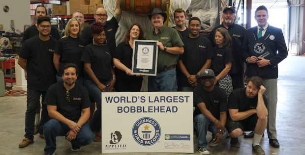 Dino and Janice Rentos, center, proudly pose with their crew and Michael Empric from Guiness World Records, right.
