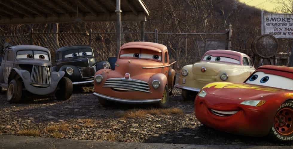 """Lightning McQueen comes hood to hood with agroup of characters who represent the roots of stock car racing. From left are River Scott (Isiah Whitlock Jr.), Junior""""Midnight""""Moon (Robert Glenn""""Junior""""Johnson), Smokey (Chris Cooper), Louise""""Barnstormer""""Nash (Margo Martindale), and Lightning himself (Owen Wilson)."""