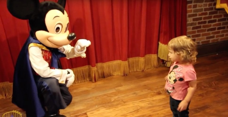 Mickey mouse talking to a little girl