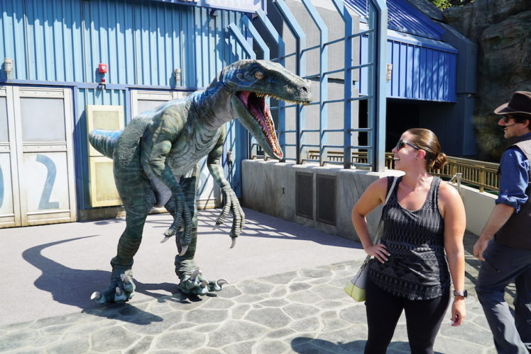 Blue the dinosaur meets a guest at Jurassic World in Universal Studios Hollywood, representing the future of the Jurassic Park / World franchise.