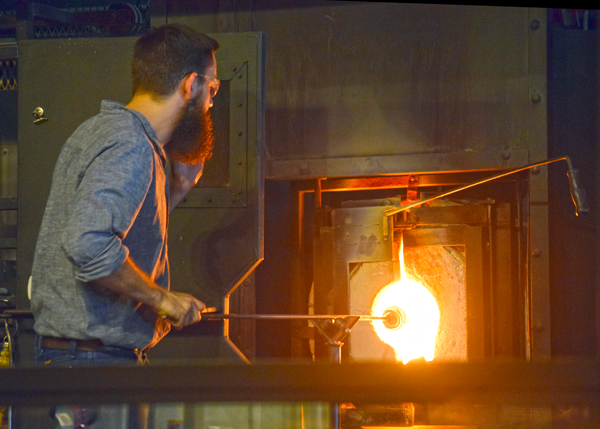 Glassmaker works with molten glass in kiln at Silver Dollar City