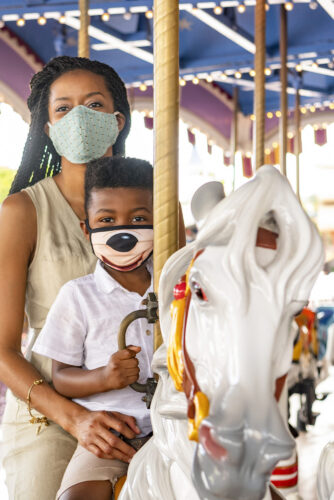 A mother and son ride the carousel at Magic Kingdom while wearing face masks.