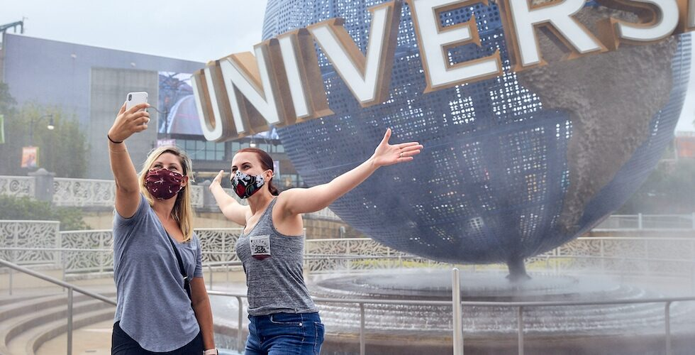 Two girls pose in front of Universal's globe with their face masks on.
