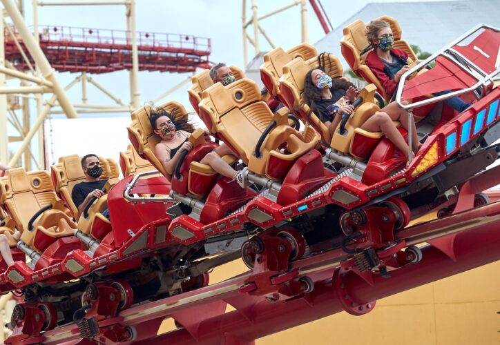 Fans ride a roller coaster with face masks on at universal studios florida.