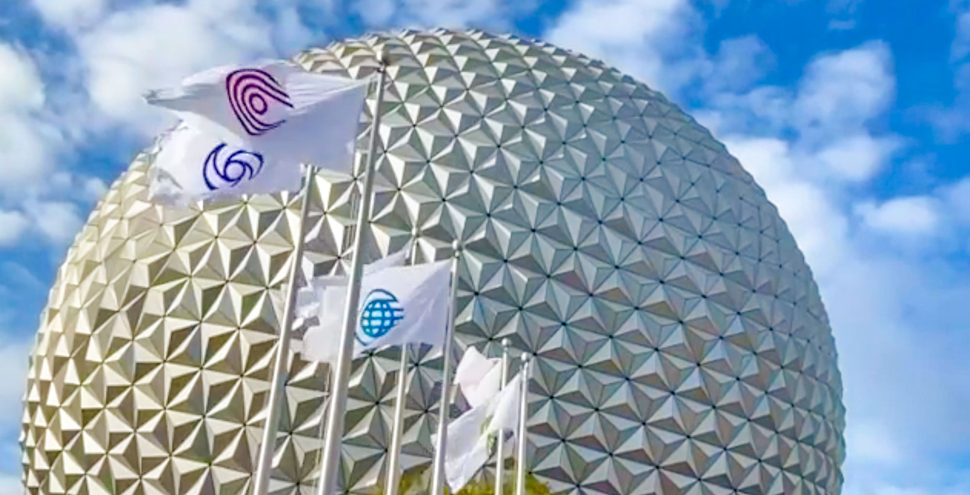 Epcot icon flags in front of Spaceship Earth