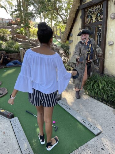 A golfer sword fighting with a pirate at Pirate's cove.