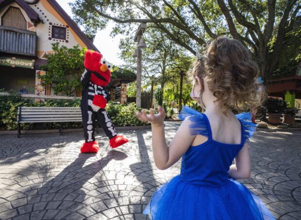 Elmo greets children, dressed in his Halloween costume